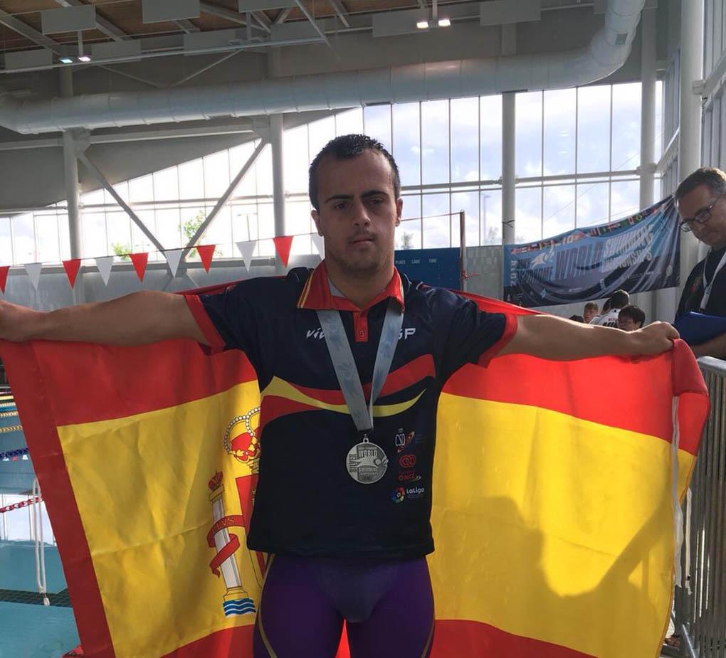 Eloy Molina posando con su flamante medalla y la bandera de España.