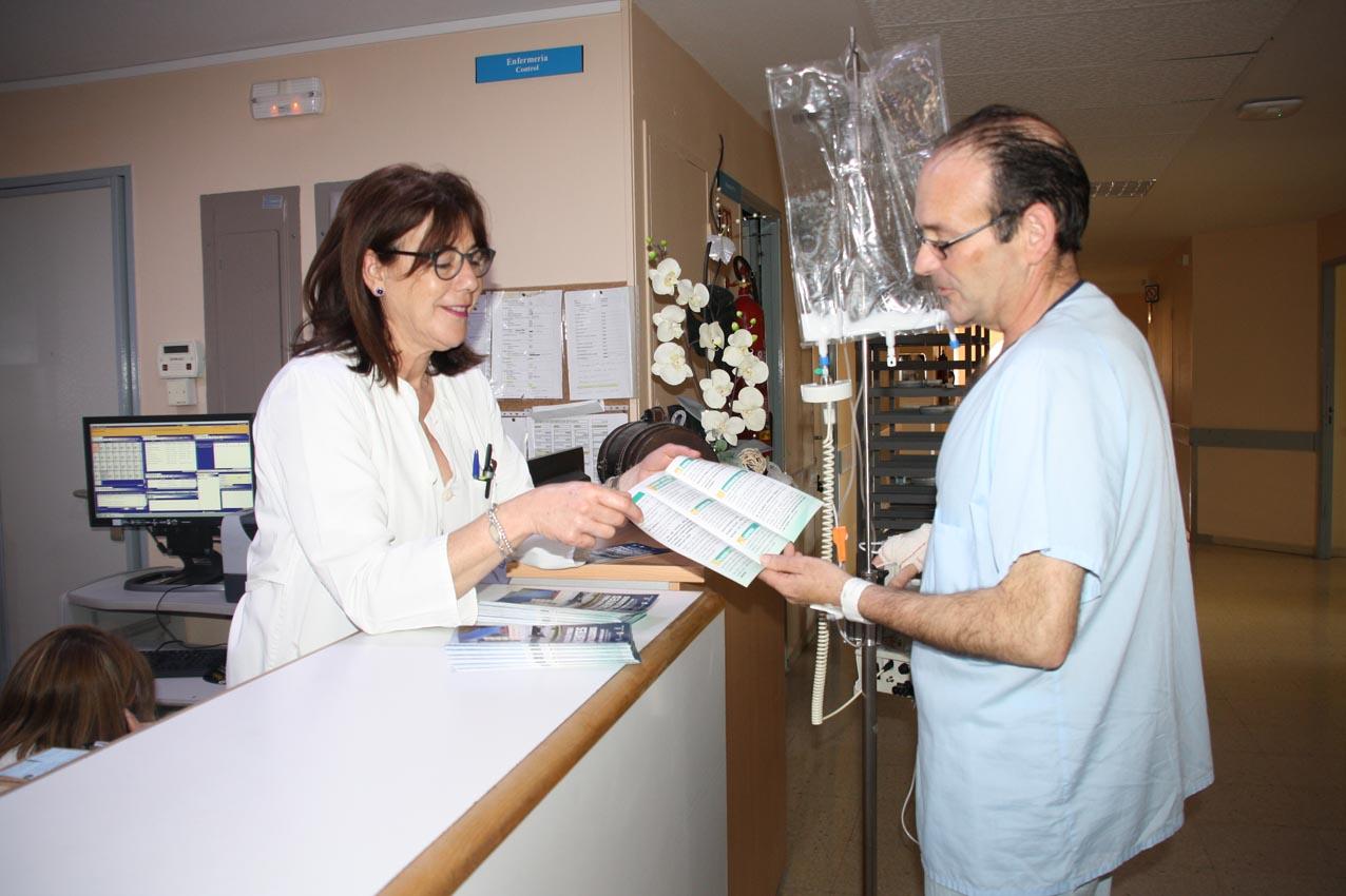 Imagen de archivo de una enfermera mostrando un folleto informativo a un paciente. Listas de espera