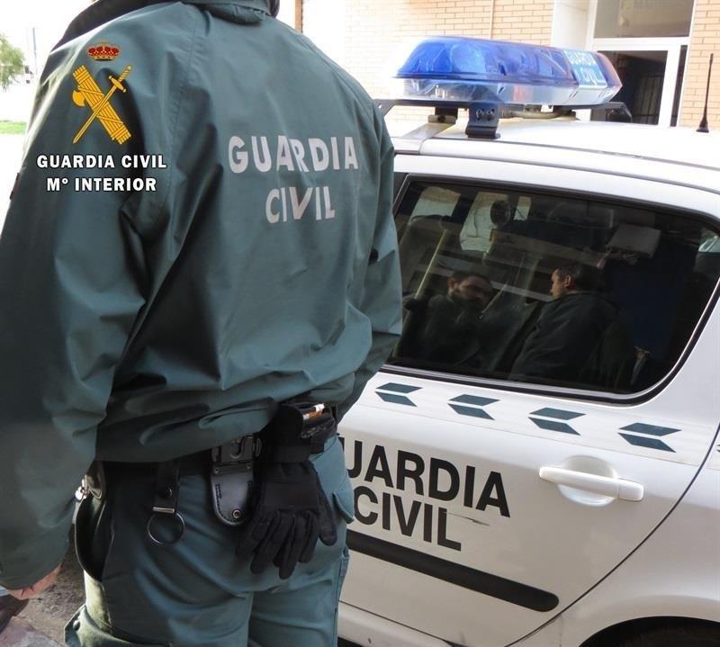 Agente y coche de la Guardia Civil.