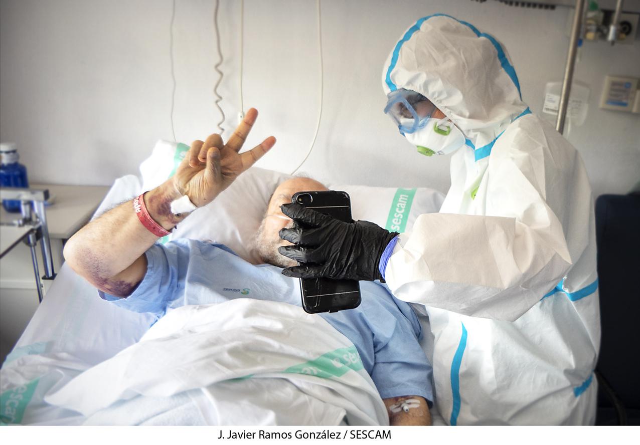 """Un paciente, ingresado semanas atrás en el hospital de Guadalajara, hace la """"v"""" de victoria con los dedos de una mano."""