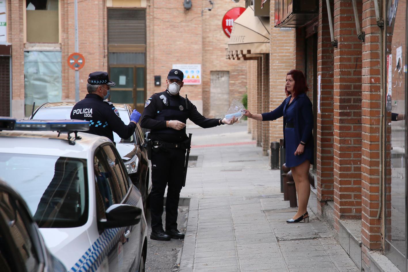 Agentes de la Policía Local entregan mascarillas en Toledo.
